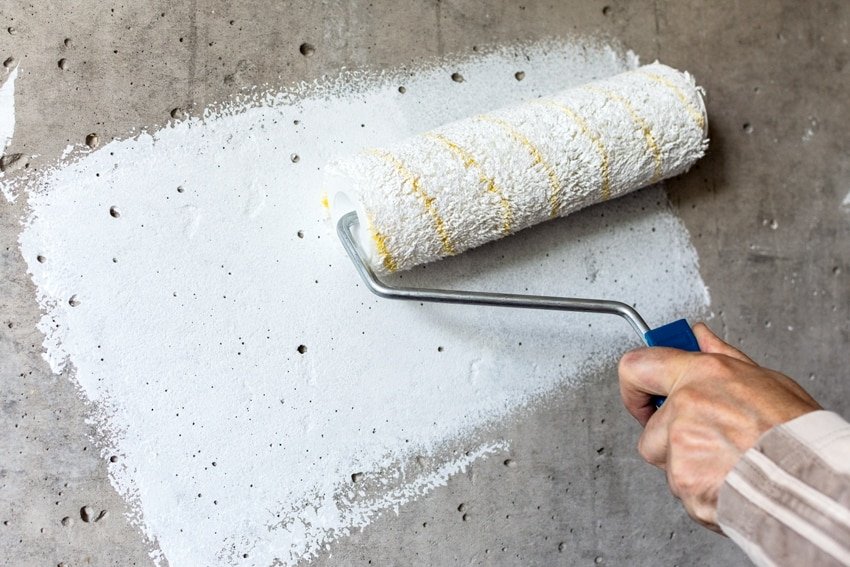 Painting a concrete wall with white paint using a white paint roller