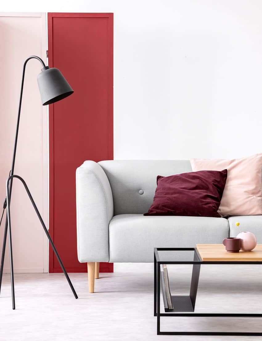 pastel pink and burgundy pillows on grey sofa in elegant scandinavian living room with burgundy pink and white wall