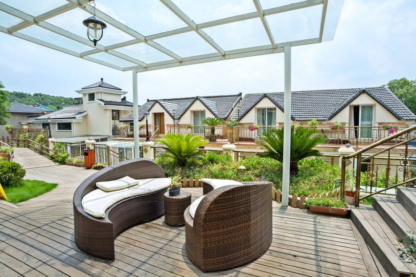 Patio with rattan sofa and wooden decking