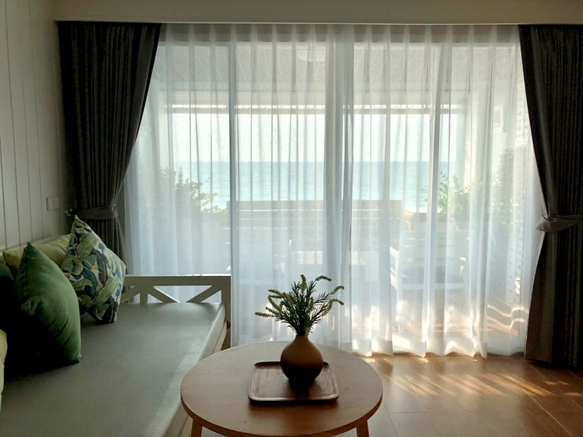 pinch pleated blackout curtains in the window of a cozy living room
