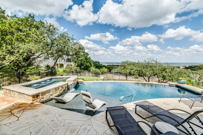 Pool with jacuzzi and chairs on ledge