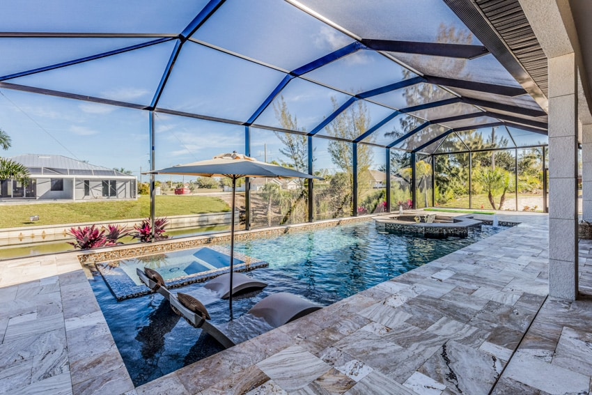 Pool with tiles and chairs on shallow ledge andglass roof