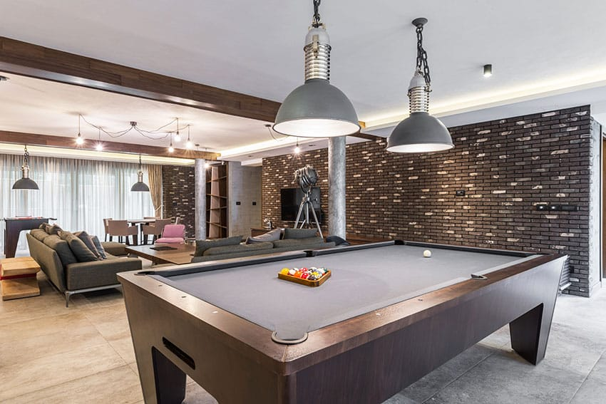 Recreational room with pool table dark stone cladding pendant lights is