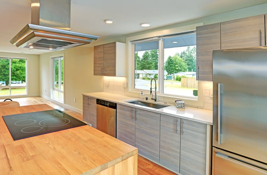 Remodeled kitchen boasts kitchen island with a hood gray shaker cabinets quartz counters and modern stainless steel appliances
