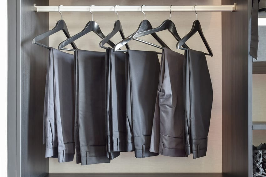 Row of pants hanging in a wardrobe