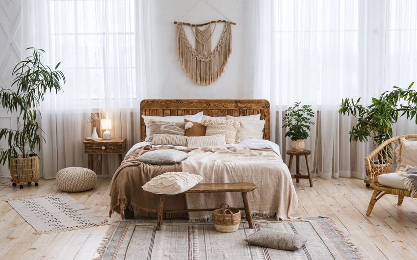 Rustic boho bedroom interior with plants rug and various decorative pieces