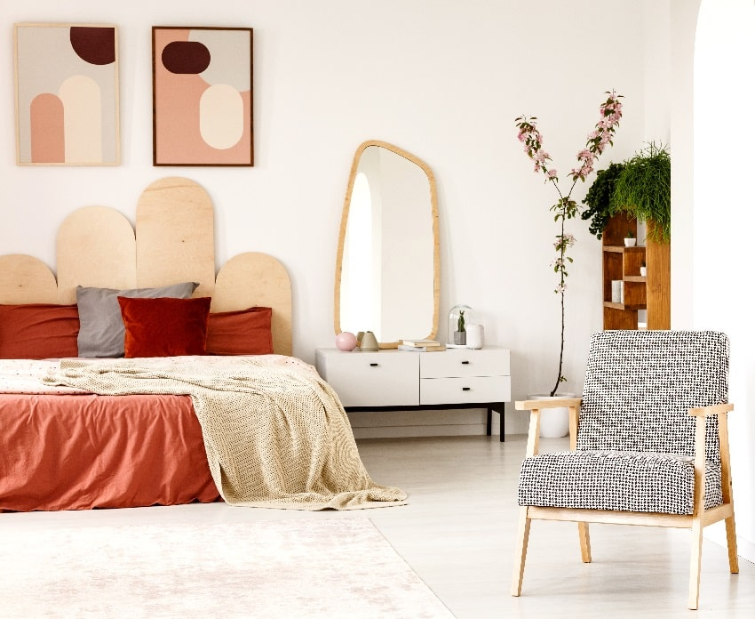 rusty bedroom interior with king size bed standing next to a white cupboard with a mirror and wooden shelves armchair and posters on wall