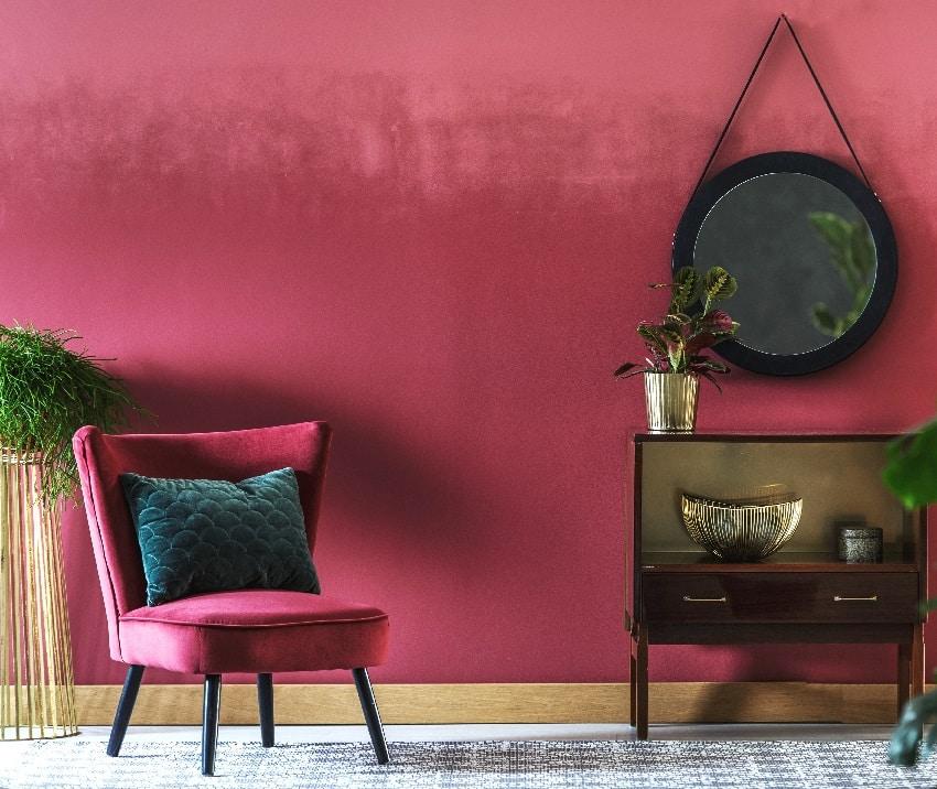 sitting room interior with burgundy armchair retro cupboard round mirror plants and dark burgundy wall
