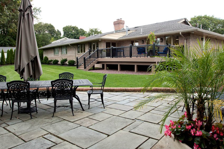 Slate patio house with deck and outdoor furniture