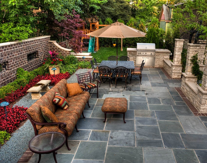 Slate patio with brown couch coffee table near garden