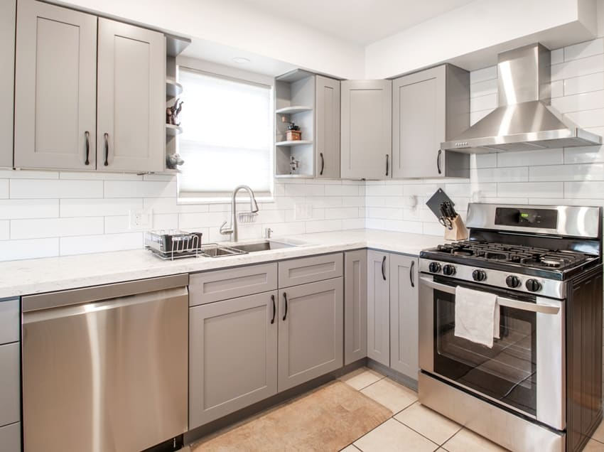 Small modern kitchen with grey cabinets and stainless steel appliances