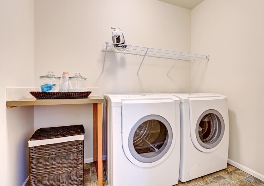small space garage laundry room with white appliances and wicker basket