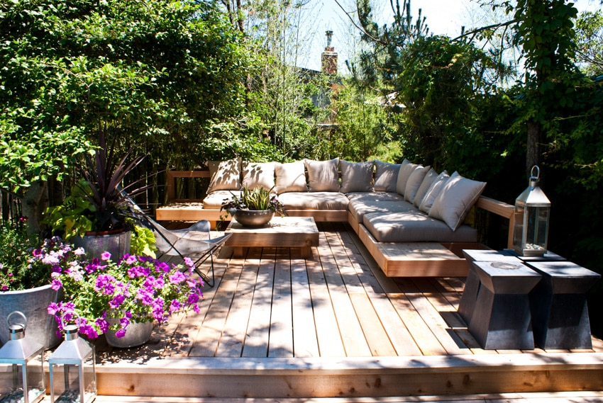 Small wood deck with sofa table flowers and trees