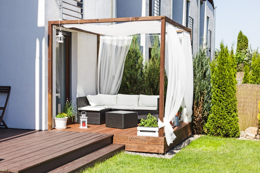 Small wood deck with white curtains
