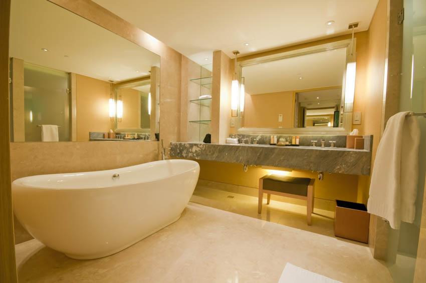 Spacious bathroom with tub concrete countertop mirror lights towel holder