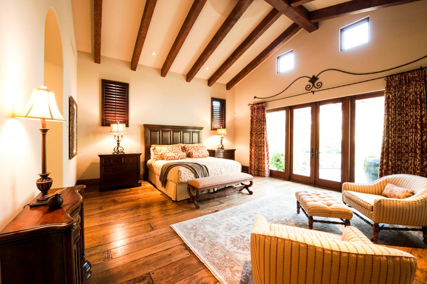 Spacious bedrooom with gold elements wood furniture floors and large windows