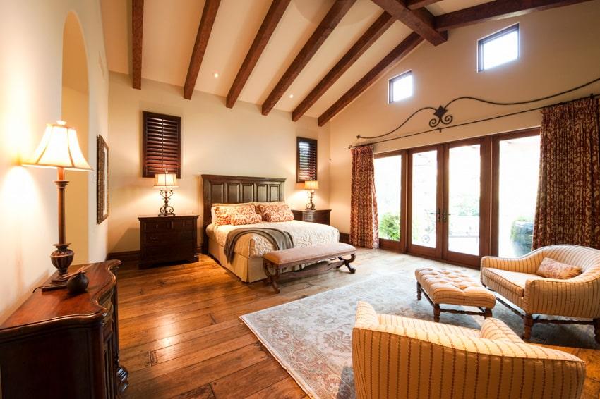Spacious bedrooom with wood furniture floors and large window