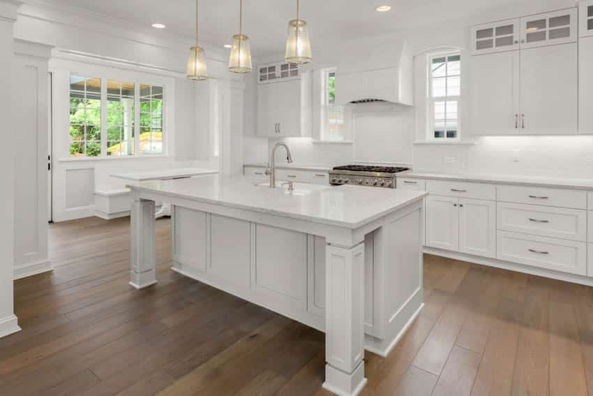 Spacious kitchen with white island and booth near windows