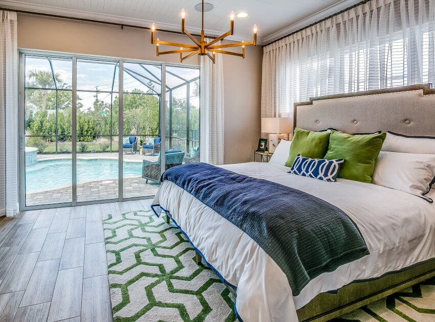 Spacious master bedroom with elegant furnishings window glass and pool outside
