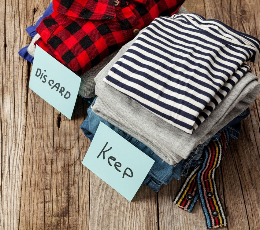 Stack of old clothes with discard or keep label