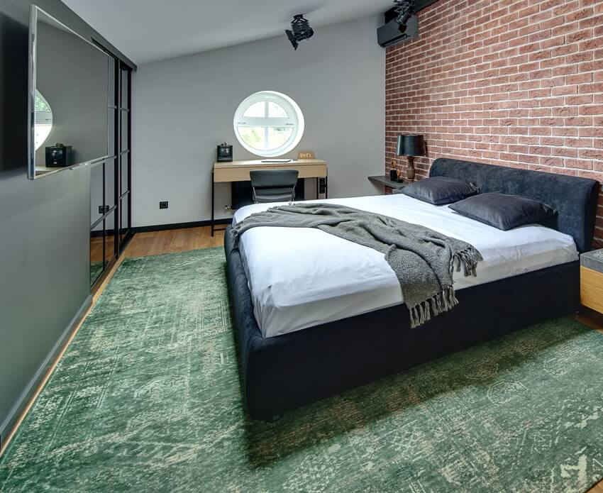Stylish bedroom in modern style with brick wall and parquet with green carpet on the floor