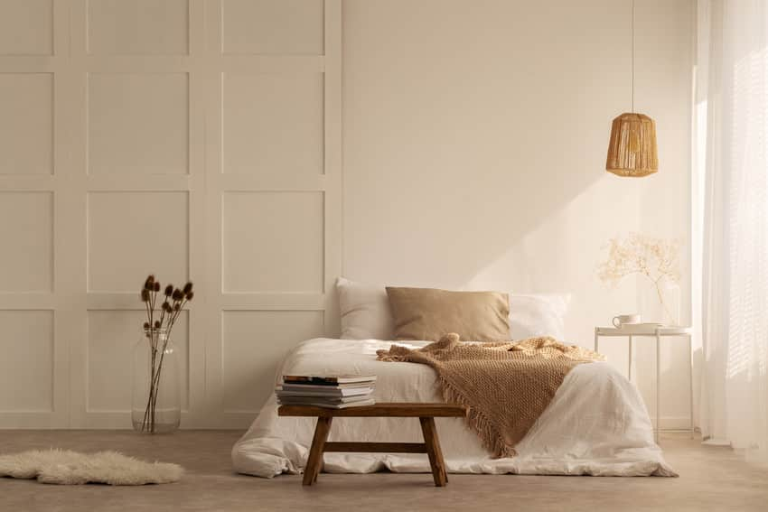 Stylish bedroom interior with beige blanket on double bed