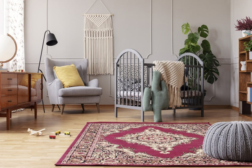 Stylish nursery with vintage furniture and red rustic rug