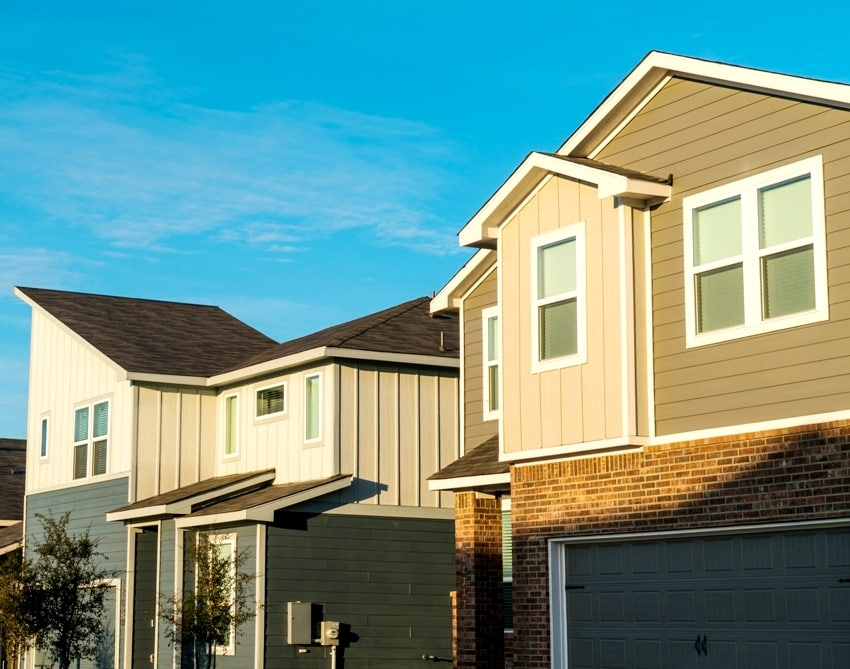 sunset light hits rooftops of modern houses in a long row in a new development suburb homes