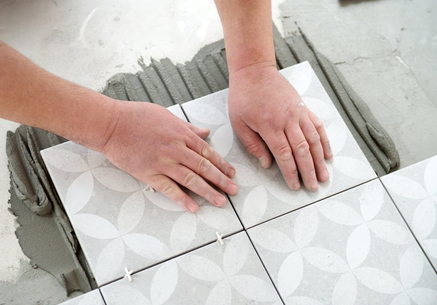Tiler laying the ceramic tile on the floor