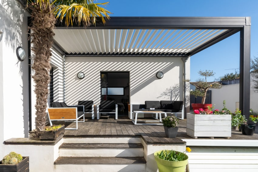 Trendy pergola with lounge chairs and metal grill