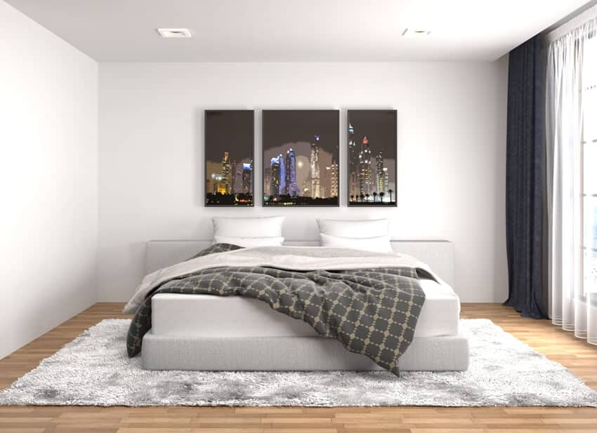 White bedroom interior with white carpet on the floor a bed and wall paint