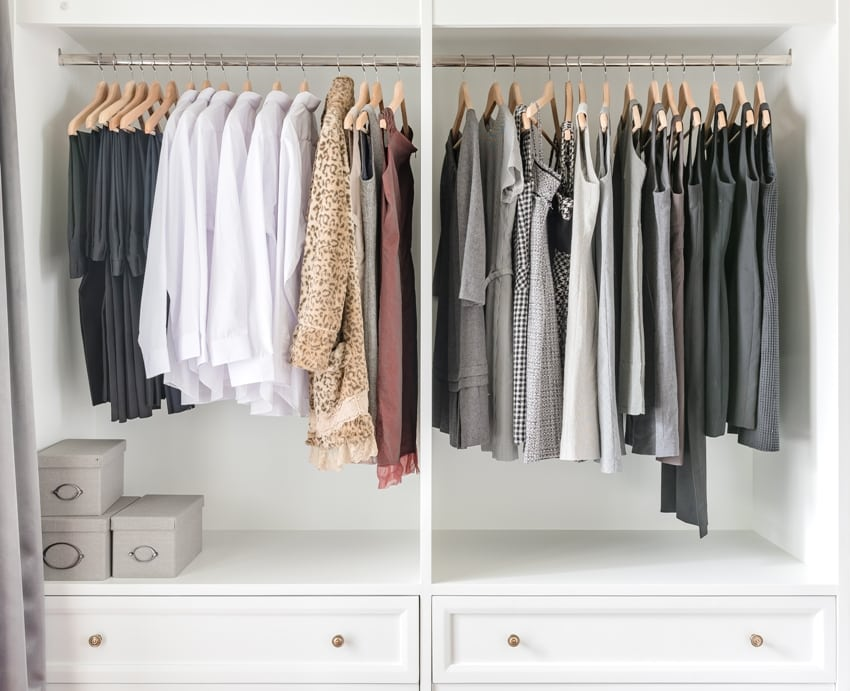 White closet with clothes hanging on rail