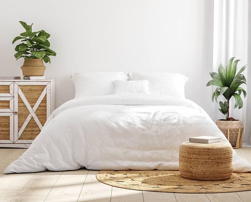 White cozy farmhouse bedroom interior with white comforter jute rug