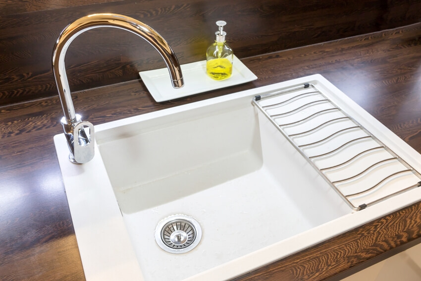 A white empty kitchen cast iron sink with liquid soap