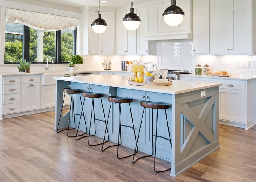White gourmet kitchen with beautiful pendant lights and light blue kitchen island trim and brown chairs