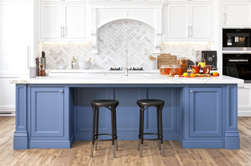 White kitchen with blue kitchen island black chairs and wooden floors