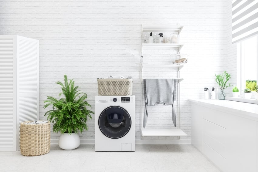 White laundry room with washer basket plant and some laundry supplies