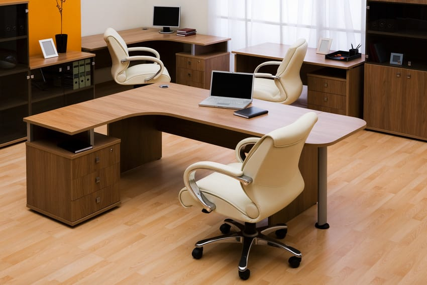 White loop arm chairs in office interior with wooden desks and flooring