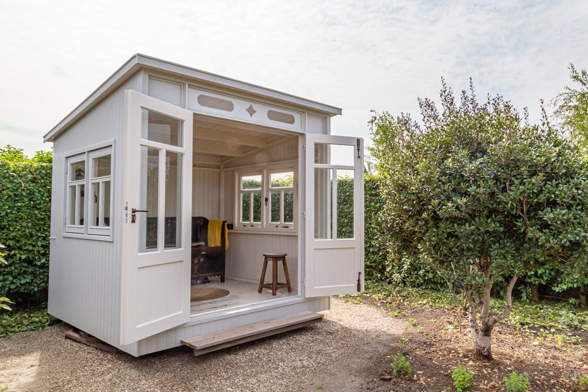 White shed doubling as sunroom in garden