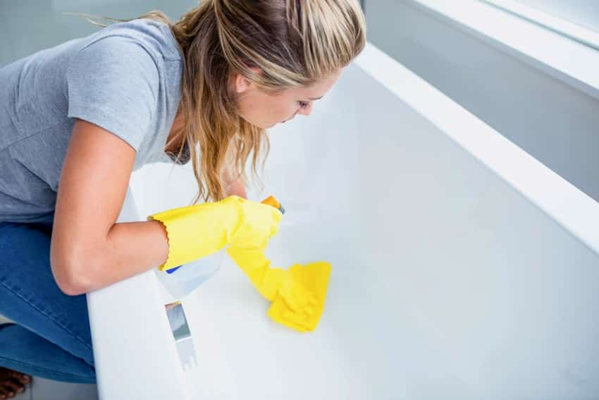 woman cleaning the bath tub in the bathroom
