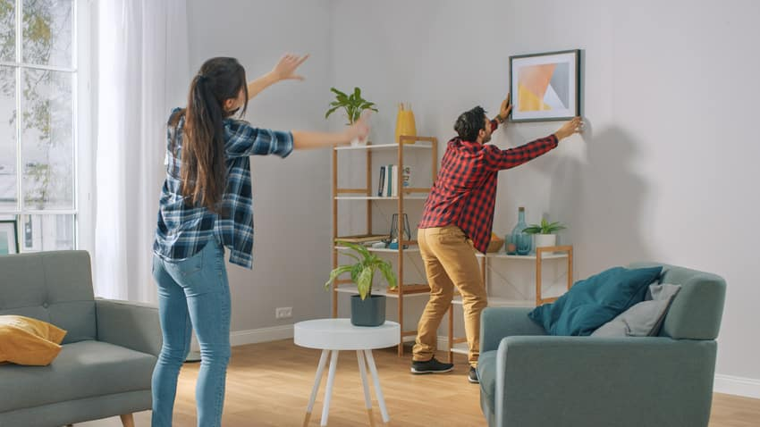 Woman instructing man how to hang frame on the wall