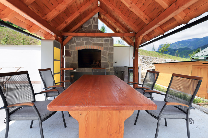 Wood covered patio with wooden long table and chairs