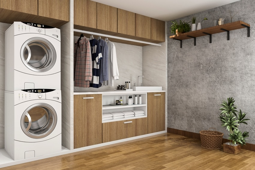 wood laminate floors laundry room with concrete wall hanged clothes washer dyer and cabinets