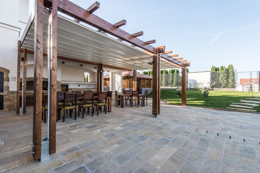 Wood pergola with aluminum canopy shade on stone patio