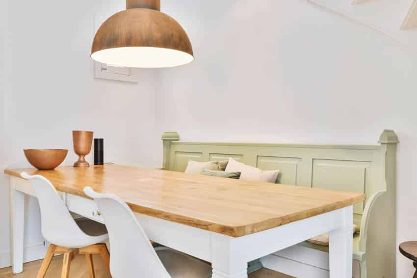 Wooden table kitchen booth hanging light white chairs