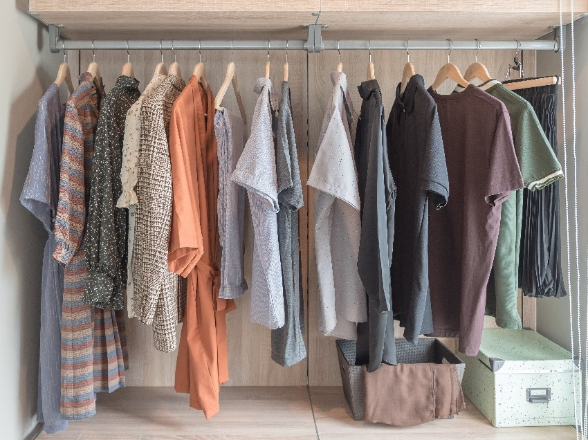 A wooden wardrobe with clothes hanging on rail