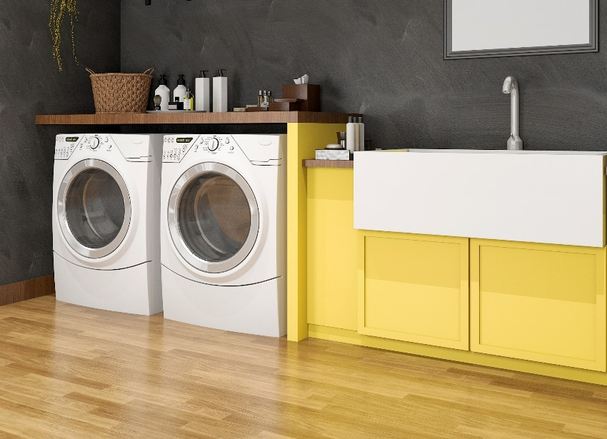 yellow sink in laundry room with loft wall and vinyl flooring