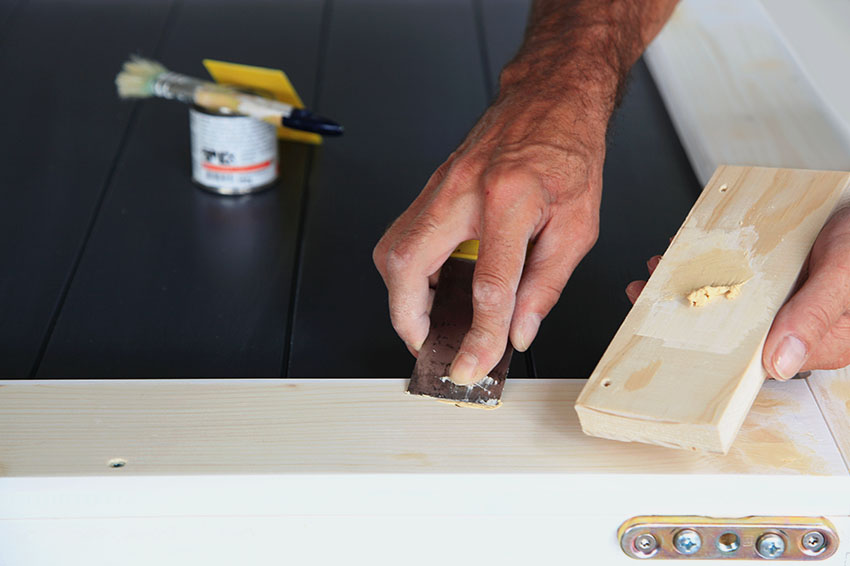 Applying wood putty to cabinet