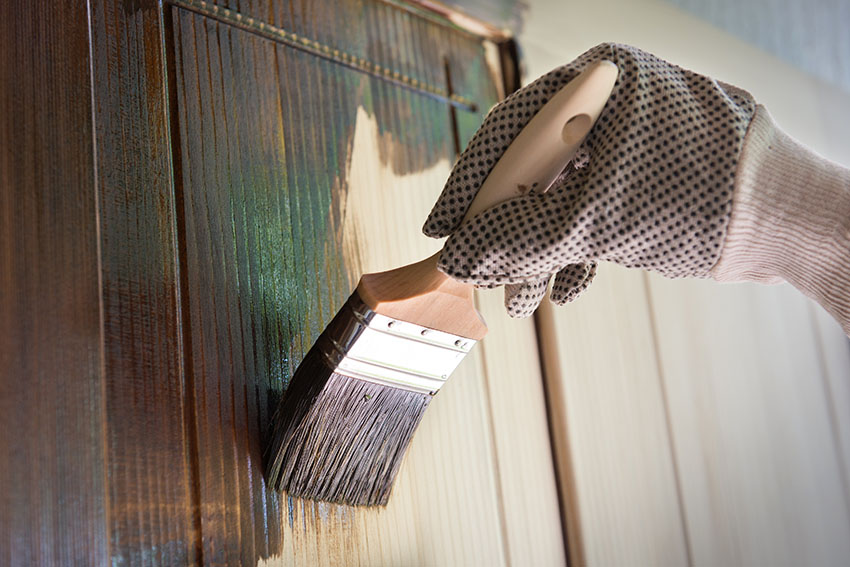 Applying wood stain on cabinet using paint brush
