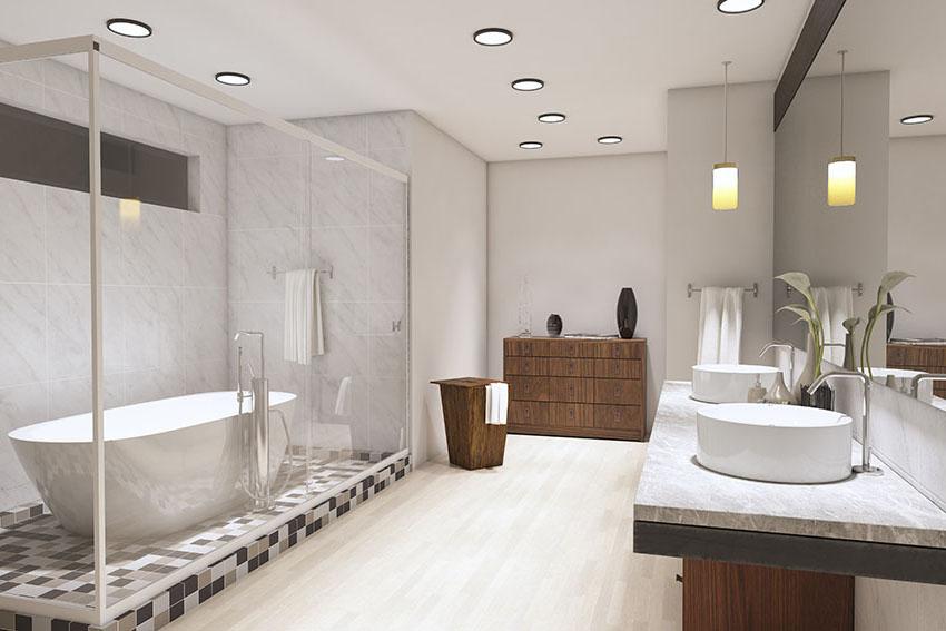 Bathroom with framed glass shower door wooden cabinet recessed lights beige tile and light gray is